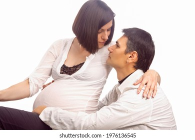 Portrait of Caucasian Man Together with Pregnant Wife Sitting Together Embraced Over White Background.Horizontal Image - Shutterstock ID 1976136545