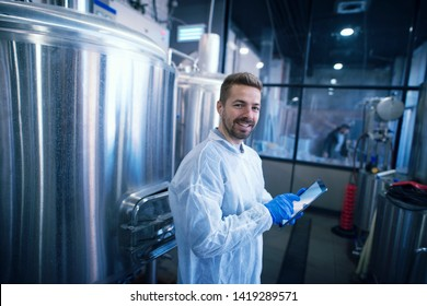 Portrait of caucasian man in white suit standing by the reservoirs in production plant. Industrial worker with tablet.