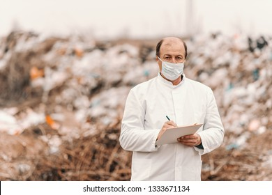 Portrait of Caucasian mature adult ecologist writing down results and looking at camera. In background landfill.