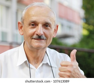 portrait of caucasian mature man with thumb up hand sign
