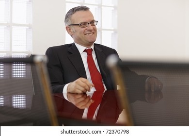 Portrait of caucasian mid adult business man talking to colleagues in meeting room. Horizontal shape, side view, copy space