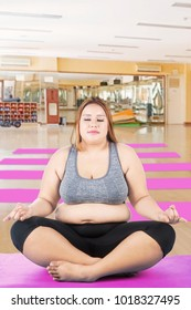 Portrait of Caucasian obese woman meditating in lotus yoga position, Shot in the fitness center