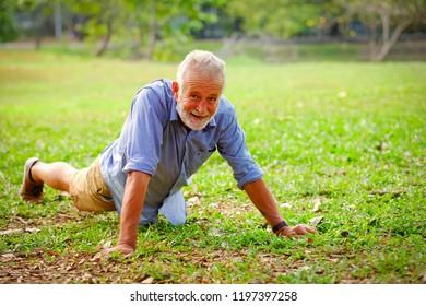 Portrait caucasian old man doing push-ups in park