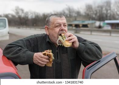 Portrait of Caucasian senior driver gobbling lyulya kebab in lavash near his car
