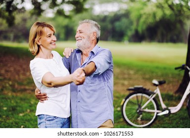 Portrait caucasian senior woman and old man, couple elder in love happy in park with bicycle