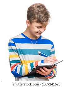 Portrait of caucasian smiling teen boy with notebook and blue pen writing something. Handsome funny teenager, isolated on white background. Happy student writing on note pad.