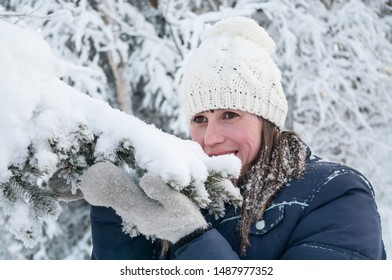 Portrait of Caucasian smiling woman touching snow cap on tree branch with her mittens, winter season