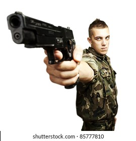 portrait of caucasian soldier with jungle camouflage pointing with pistol over white background
