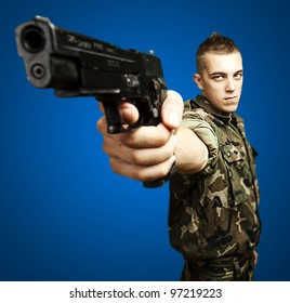 portrait of a caucasian soldier with a jungle camouflage pointing with a pistol over a blue background