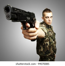 portrait of caucasian soldier with jungle camouflage pointing with pistol over grey background