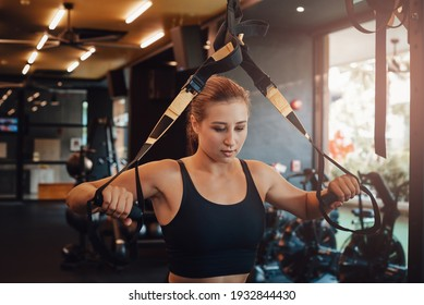 Portrait of a caucasian sportswoman in black shirt doing physical exercise with a training apparatus in gym in daytime.
