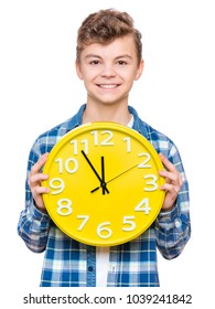 Portrait of caucasian teen boy with clock. Funny teenager showing yellow clock, looking at camera. Child back to school, isolated on white. Education and time concept or last minute christmas holiday.