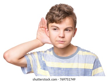 Portrait of caucasian teen boy listens to gossip. Handsome teenager wearing red t-shirt hearing something, isolated on white background. Child listening by hand up to the ear.