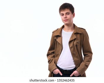 Portrait of caucasian teen boy on white background. A boy with a serious face and hands in his pockets looks straight into the camera.