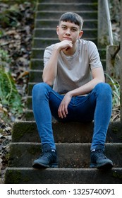Portrait of a caucasian teenage boy sitting outside on concrete steps