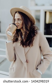Portrait of caucasian woman 20s wearing coat and eyeglasses drinking takeaway coffee while walking through city street
