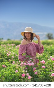 Portrait of a caucasian woman with hat standing in pink rose bush.