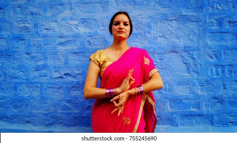Portrait of caucasian woman in traditional indian clothes. Jodhpur. Indian gesture, sign. Namaste - welcome. Beautiful background.