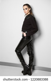 Portrait of caucasian woman in zipper sweater with leather inserts and faux leather pants posing against white wall.