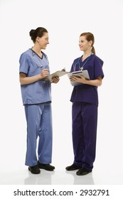 Portrait of Caucasian women doctors in medical scrubs standing talking holding medical charts against white background.