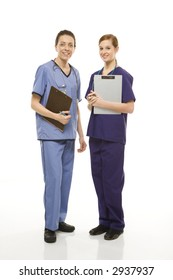 Portrait of Caucasian women doctors in medical scrubs standing holding medical charts against white background.