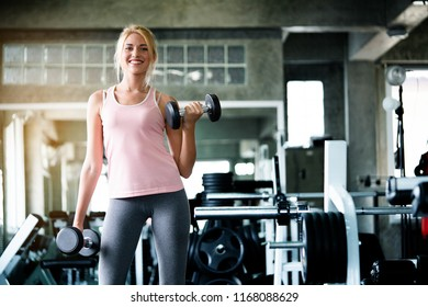 Portrait Caucasian women wearing pink tightening exercises are lifting dumbbell. To build muscle upper arm to tighten in gym which is a set to help keep the body healthy. concept health care and sport