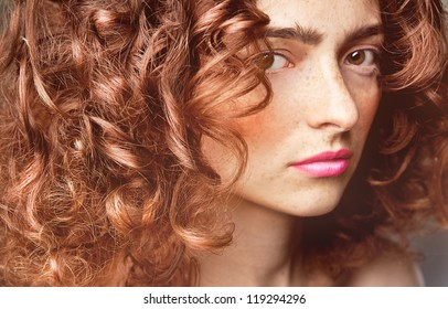 Portrait of  caucasian young woman with beautiful red  curly hair