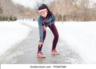 Portrait of Caucasian young woman feeling pain in legs after jogging outside in winter park. Girl having injury when running excercising  outdoors in cold weather conditions