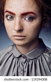 Portrait of  caucasian young woman with freckles posing on grey background