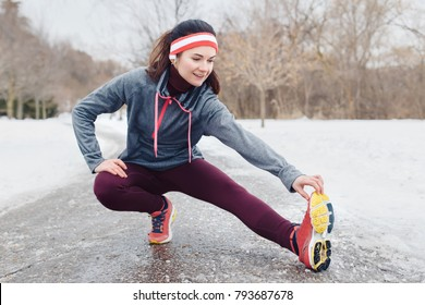 Portrait of Caucasian young woman stretching and warming up for jogging outside in winter park. Girl exercising outdoors wearing sportswear, headband and headphones.