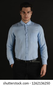 Portrait of Caucasian,masculine, slicked back hair, handsome man in light blue shirt, black slack, standing, right hand in pocket,straight face, looking straight to camera on black background