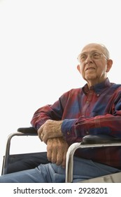 Portrait of Caucasion elderly man sitting in wheelchair with hands clasped.