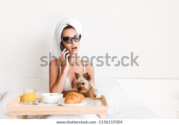Portrait of a celebrity woman in sunglasses and towel around her head having breakfast while sitting with a tray in bed with her dog and talking on mobile phone