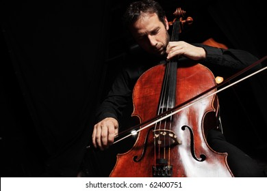 Portrait of cellist playing classical music on cello on black background. Copyspace.