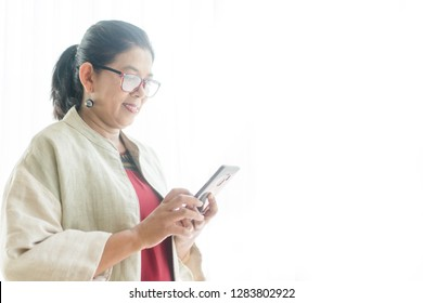 Portrait of CEO Senior Woman talking and touching on her mobile phone on white background near the window on office.Senior woman has a happy conversation at cellphone and Smiling face.