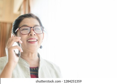 Portrait of CEO Senior Woman talking on her mobile phone on white background near the window on office.Senior woman has a happy conversation at cellphone and Smiling face.