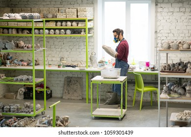 Portrait of Ceramist Dressed in an Apron Working on Clay Sculpture in the Bright Ceramic Workshop.