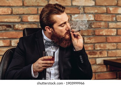 Portrait of a charismatic attractive man sitting on a chair and holding a glass of whiskey in his hand and smoking a brown cigar against a brick wall background. Style concept