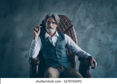 Portrait of charismatic elegant old man boss company owner sit chair hold cigar wear white shirt brown pants trousers isolated over grey color background