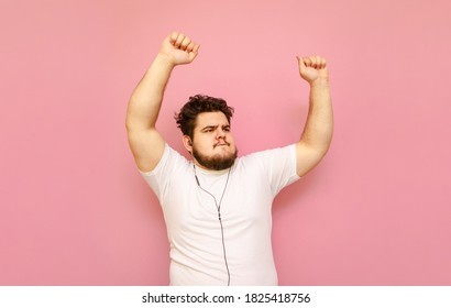 Portrait of charismatic fat man listening to music in headphones and dancing on pink background wearing white t-shirt. Curly overweight man dancing to music in headphones, isolated.