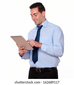 Portrait of a charismatic latin guy on blue shirt using his tablet pc on isolated background