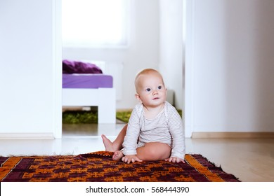 Portrait of charming 8-9 month old baby child at home interior. Curious, smiling child explores the world around. Cute baby sitting on the floor.