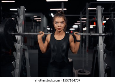 Portrait of charming active powerlifter taking photo with heavy professional barbell in hands, trying to lift barbell above head, holding metal bar on shoulders, looking straight with serious face