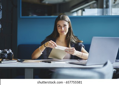 Portrait of charming administrative manager satisfied with occupation receiving mail from delivery service with business documentation,secretary holding envelope with letters sitting in office