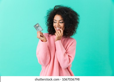 Portrait of charming american woman 20s with afro hairstyle holding plastic credit card with pleasure isolated over blue background