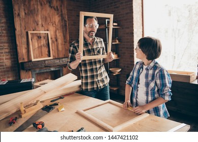 Portrait of charming attractive dad kid hold hand window wooden having fun funny funky content show dressed shirt plaid trendy stylish workstation professional indoors glasses goggles protective