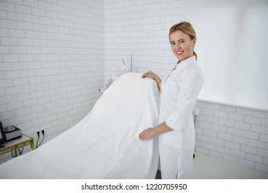 Portrait of charming beautician in white lab coat standing near daybed covered with sheet. She is looking at camera and smiling