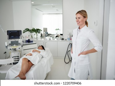 Portrait of charming beautician in white lab coat looking away and smiling. Brunette woman in bathrobe lying on daybed