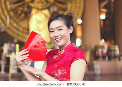 Portrait charming beautiful asian woman: Attractive young lady gets red envelopes from her family. Pretty girl shows red envelopes. Gorgeous girl feel happiness and she has nice smile, chinese dress