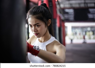 Portrait charming beautiful boxer woman: Attractive girl is practicing boxing. Gorgeous girl is punching target. Pretty girl loves exercise, especially Thai Boxing. She looks determined, confident
